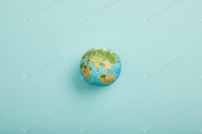 vista superior del modelo del planeta sobre fondo turquesa, concepto de día de la tierra