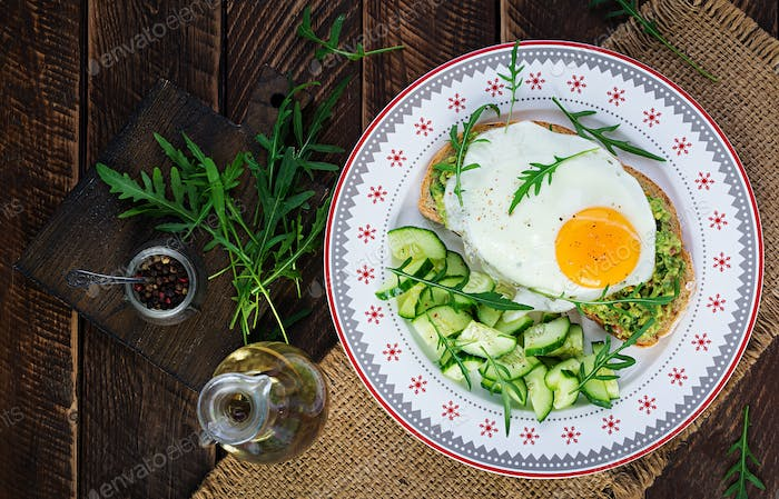 Avocado sandwich with fried egg and cucumber with arugula on wooden table