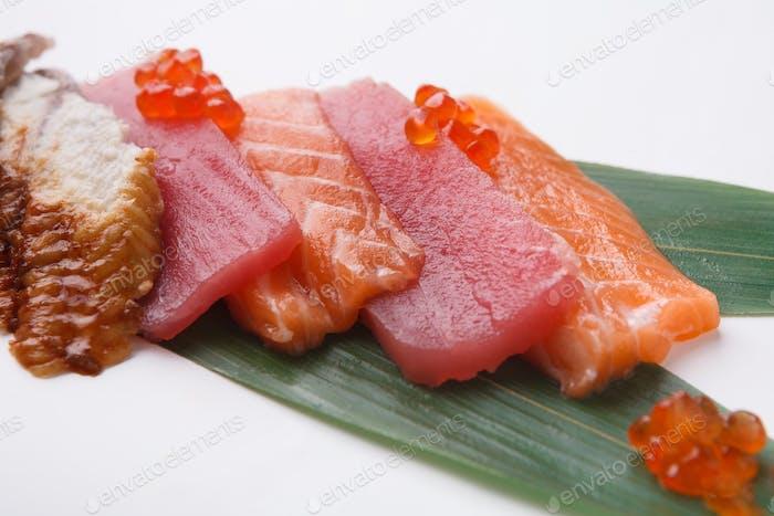 Sashimi set on bamboo leaf isolated at white, closeup