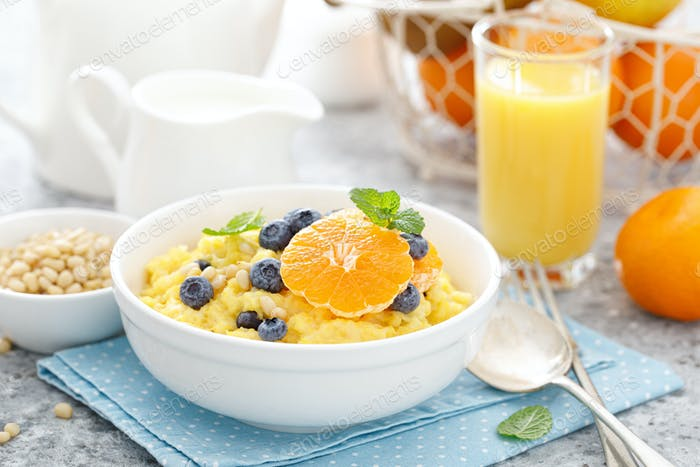 Corn porridge with fresh blueberry, orange and pine nuts in bowl served for breakfast