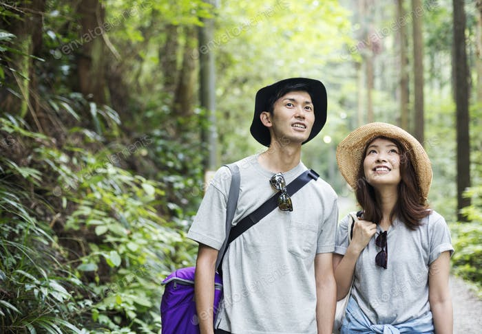 Smiling young woman and man standing in a forest.