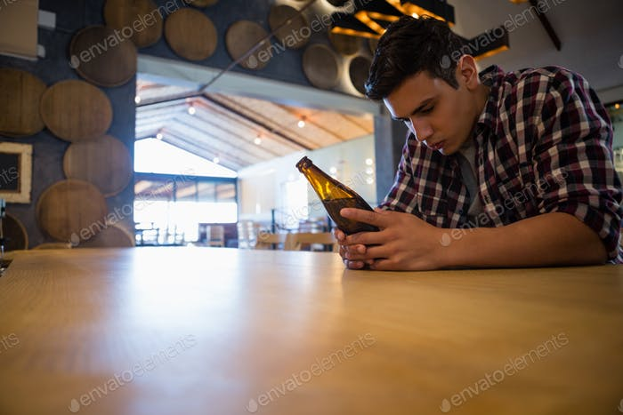 Sad man with beer bottle at bar