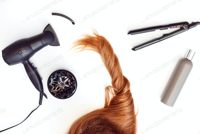 Set of tools dryer, iron and hair brush for hairstyle and red hair on white