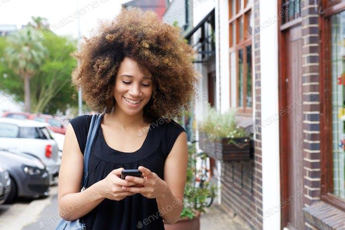 Glückliche schwarze Frau zu Fuß und Lesen Textnachricht