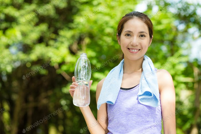 Female runner resting and drinking water