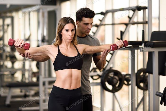 Personal Trainer hilft einer jungen Frau Gewichte zu heben