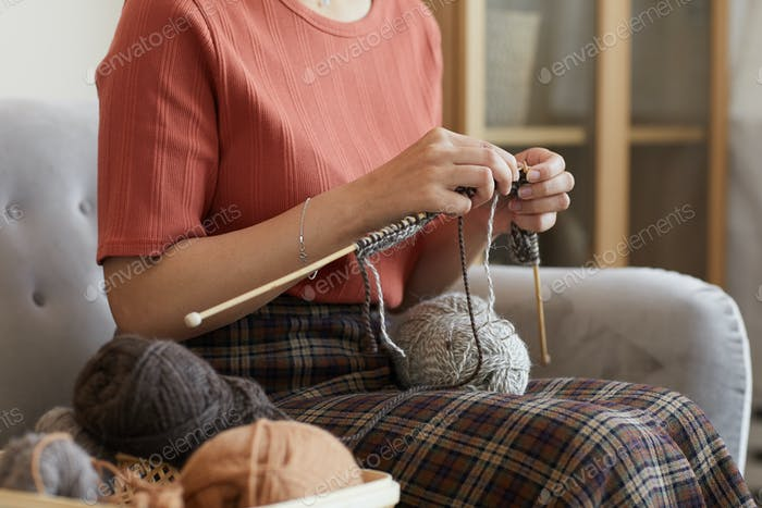 Woman knitting the scarf