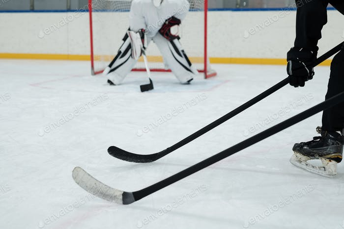 Hockey sticks held by two players in sports uniform on background of goal keeper