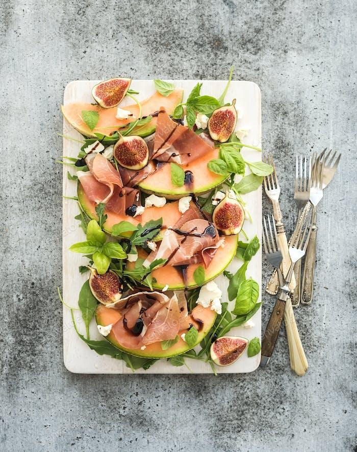 Schinken, Melonen, Feigen- und Weichkäse-Salat auf weißem Servierbrett über Grungegrund