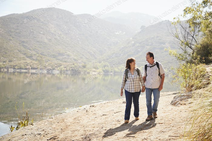 Senior couple hiking by a mountain lake