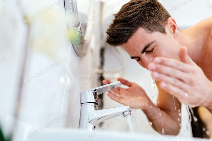 Handsome man washing face in bathroom