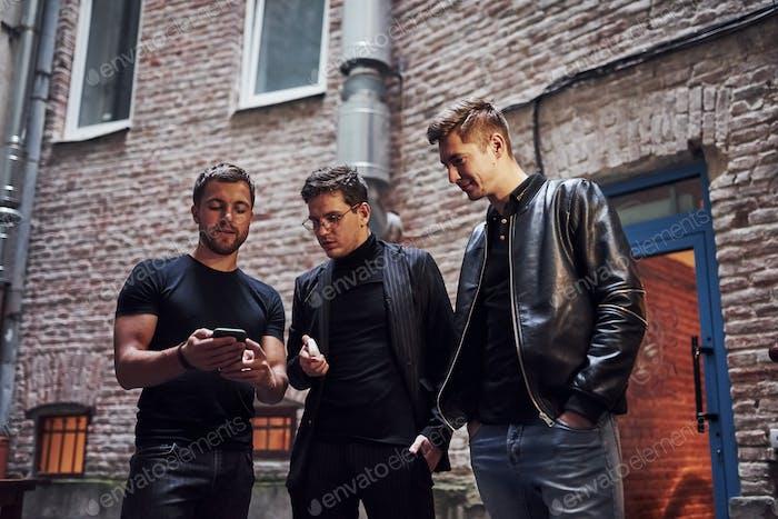 Ein paar lustige Sachen. Drei männliche Freunde stehen vor der Bar. Konversation haben. In schönen Kleidern