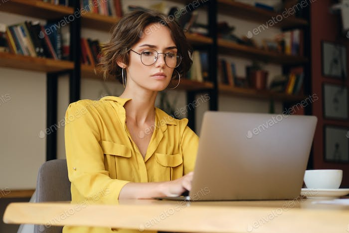 Young businesswoman in eyeglasses thoughtfully working on new project with laptop