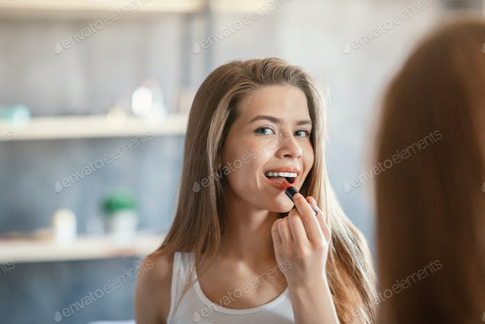 Beauty and makeup. Pretty lady applying lipstick near mirror indoors