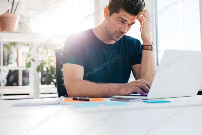 Young man using laptop and looking worried