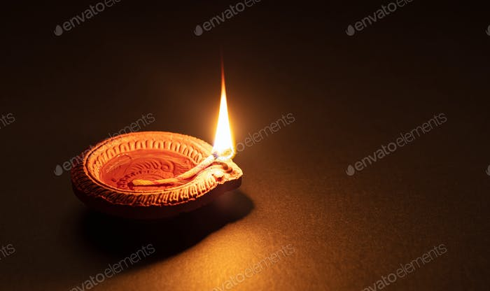 Diwali, Hindu festival of lights celebration. Diya oil lamp against dark background,