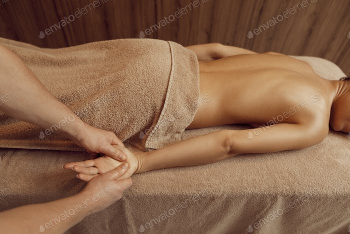Male masseur pampering hands to young woman