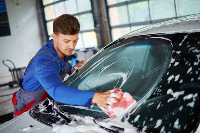 Man worker washing windshield with sponge on a car wash