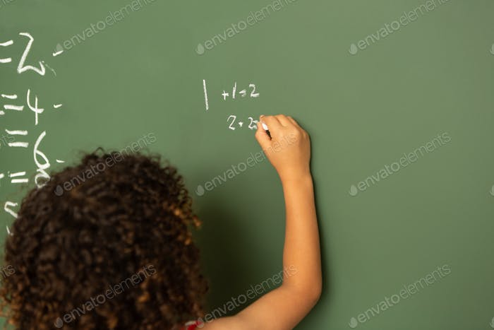 schoolgirl solving mathematics calculations on green board in classroom at school