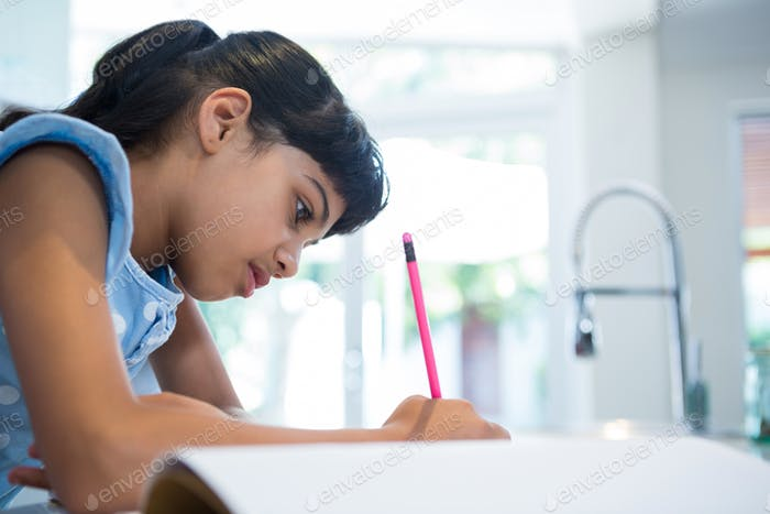 Side view of girl writing in book