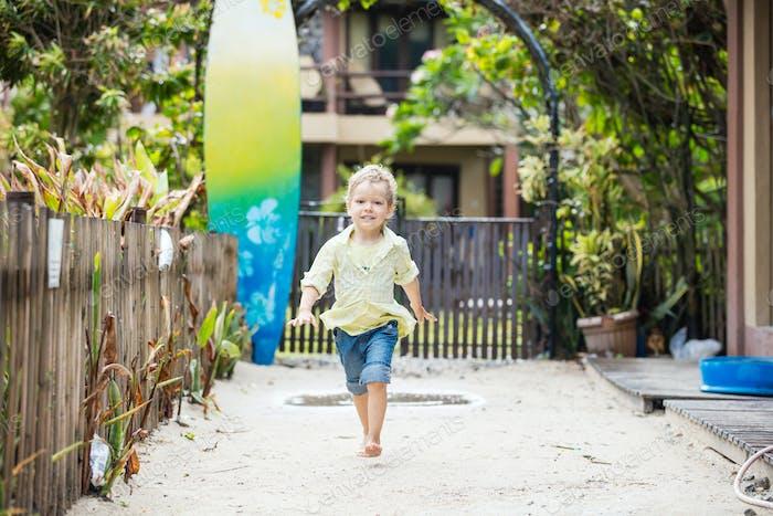 Cute blonde boy walking barefoot in tropical resort