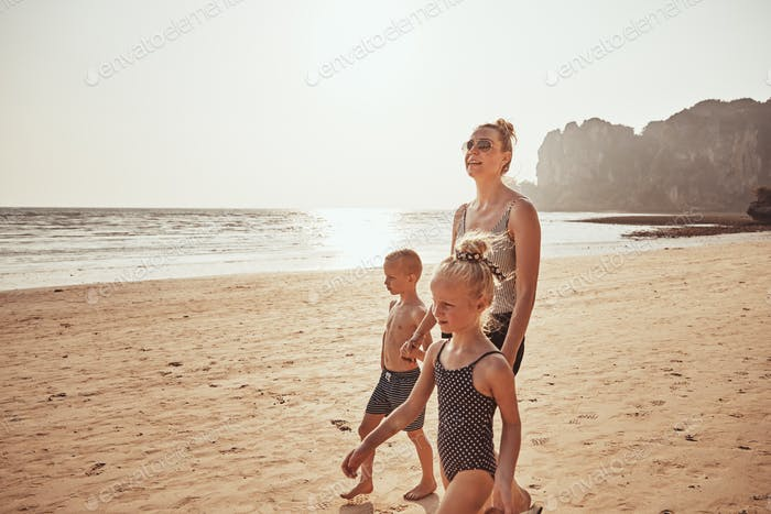 Smiling Mom and two children walking along a sandy beach