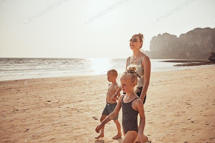 Lächelnde Mama und zwei Kinder zu Fuß entlang eines sandigen Strandes