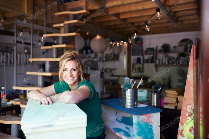 Portrait Of Woman In Workshop Upcycling And Working On Furniture With Sandpaper