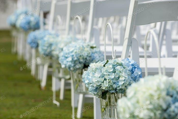 Sträuße von Hortensien hängen von Stühlen für Hochzeit im Freien.
