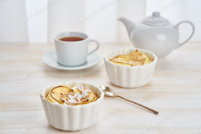 Apple cake and cup of tea on white wooden table in kitchen.