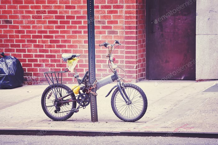 An old bicycle locked to a sign post in Chinatown, NYC, USA.