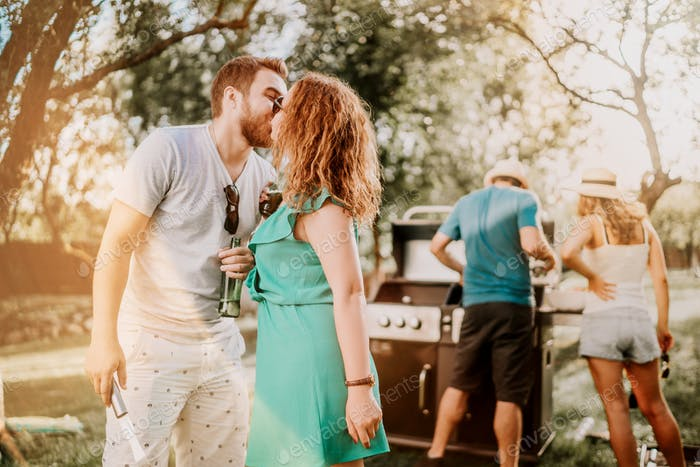 Portrait of perfect caucasian couple kissing at barbecue party, friends having a good time