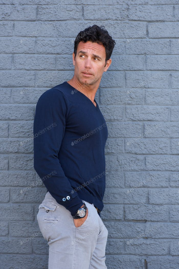 Handsome man leaning against gray wall