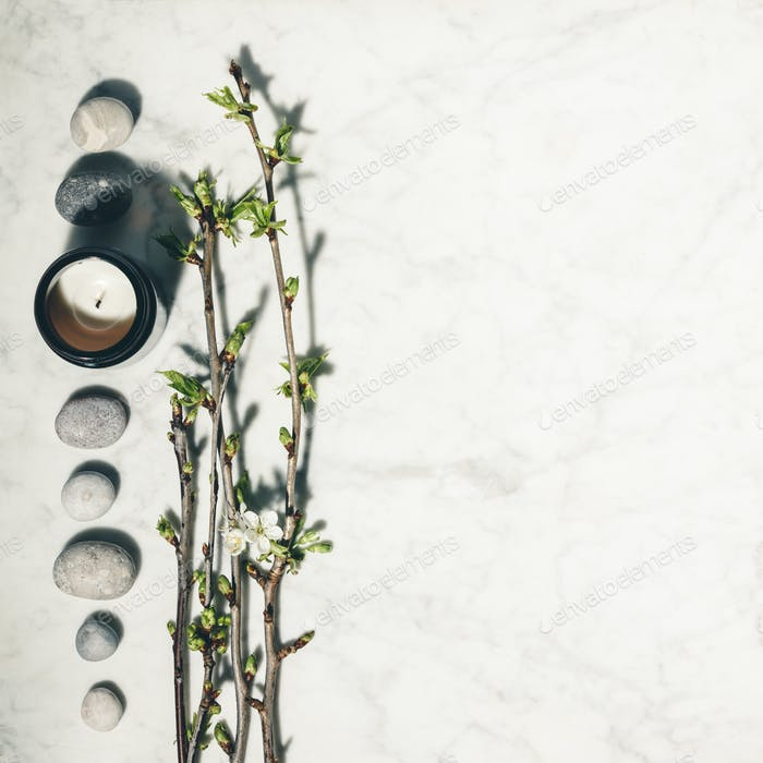 spring cherry branches, natural candle and grey stones on white marble background.