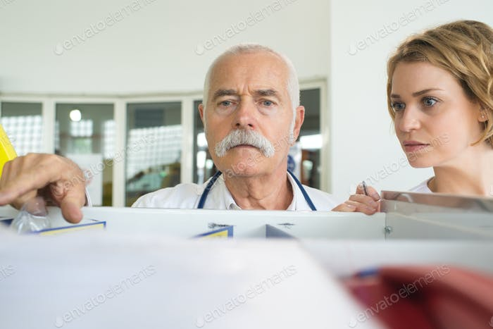 male doctor standing in front of shelves in drug store
