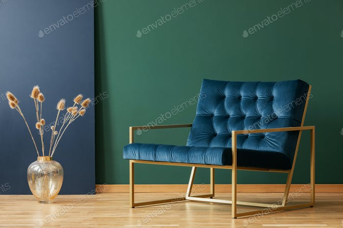 Plant in gold vase next to armchair in blue and green elegant living room interior. Real photo