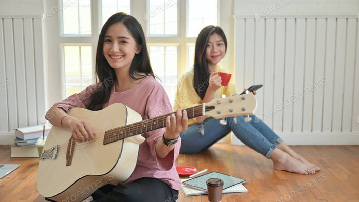 Teenage girls are singing and playing guitars.They stay at home to prevent the coronavirus outbreak.