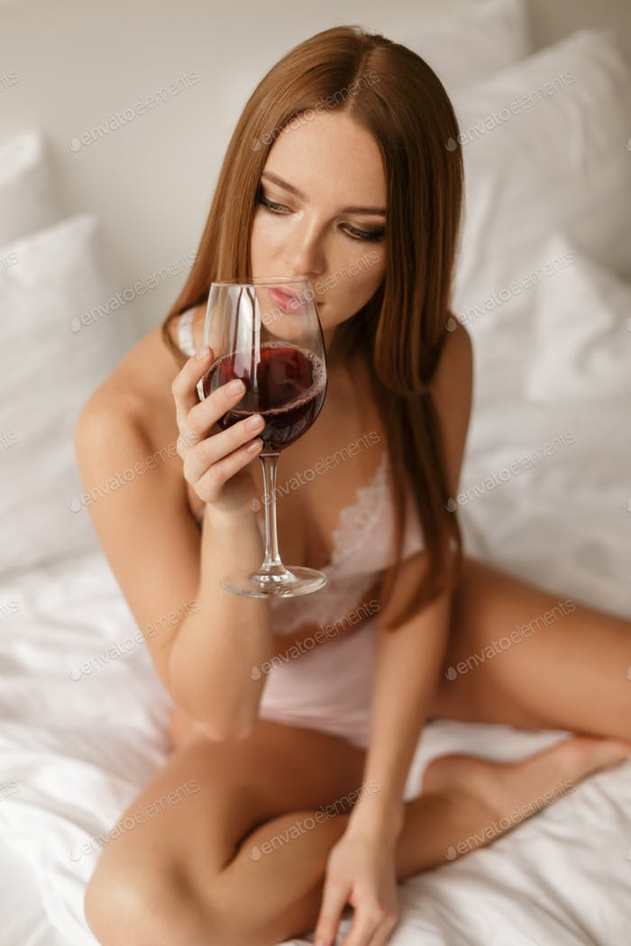 Portrait of young beautiful lady sitting in bed and drinking red wine thoughtfully looking aside