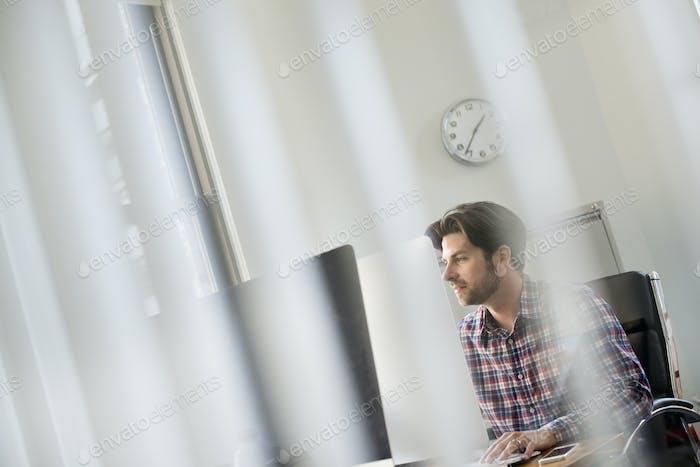 Ver a través de una partición de oficina de un hombre sentado en un escritorio.