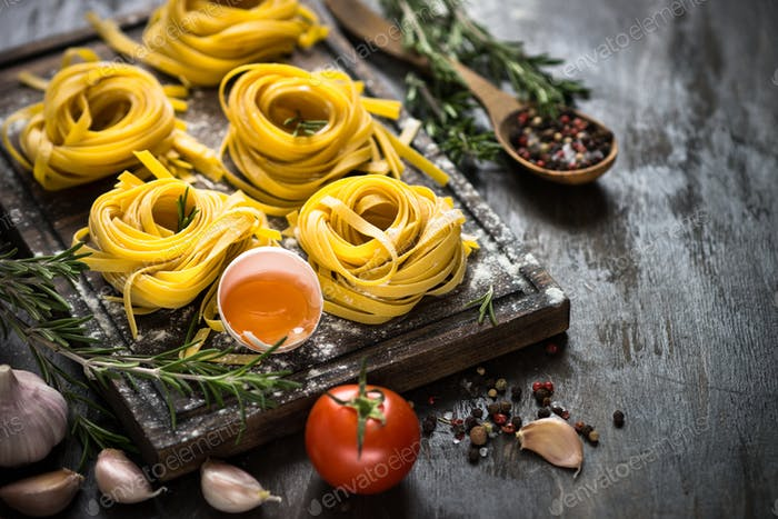 Fresh raw pasta tagliatelle and ingredients