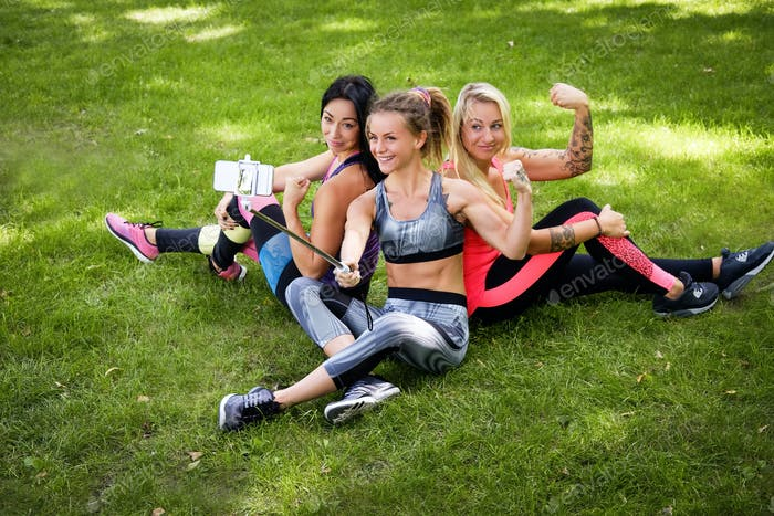 Three sportive female friends at the park outdoors make selfie on a phone with a stick, smiling.