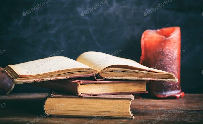 Vintage Bücher und Kerze auf Tafelhintergrund