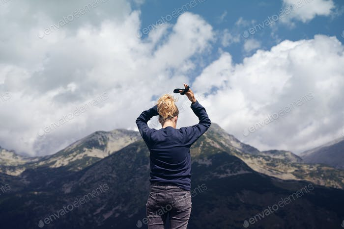rear view of woman arranging her hair in front of a mountain range