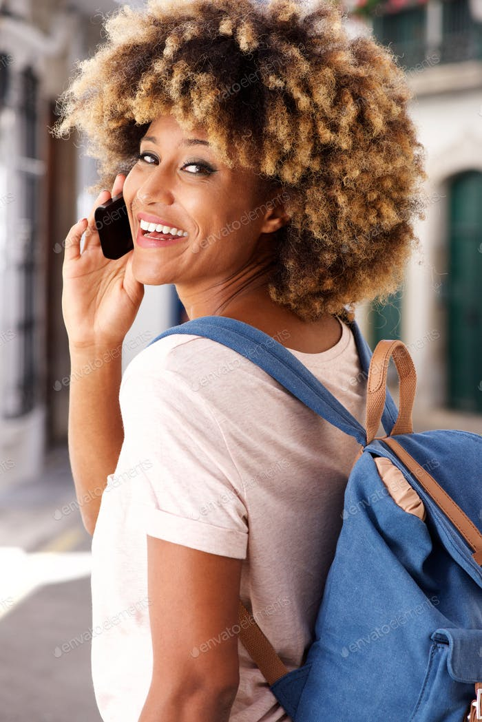elegante joven negro Mujer de pie al aire libre y hacer llamada telefónica