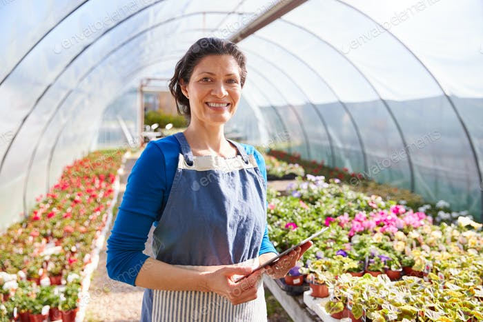 Portrait Of Mature Woman Working In Garden Center Greenhouse With Digital Tablet And Checking Plants