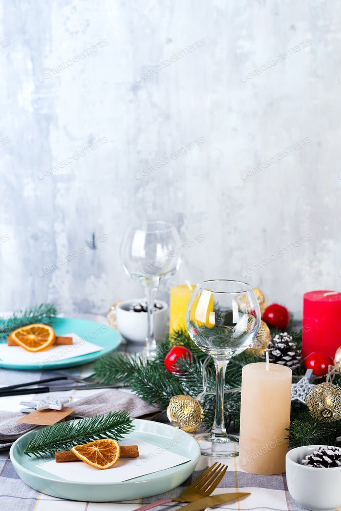 Festive Christmas and New Year table setting with dry orange and cinnamon on a gray textile. Dining