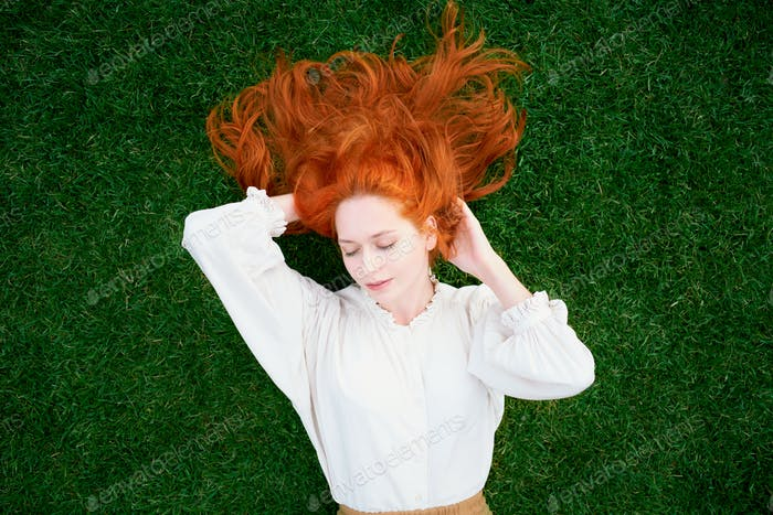 Beautiful girl with red hair lying on green grass with closed eyes