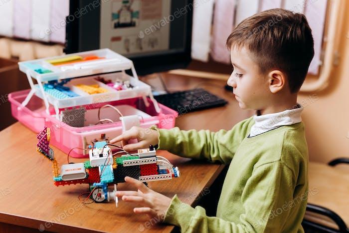 Fleißig Junge in grünen Pullover gekleidet sitzt am Schreibtisch mit Computer und macht den Roboter aus dem