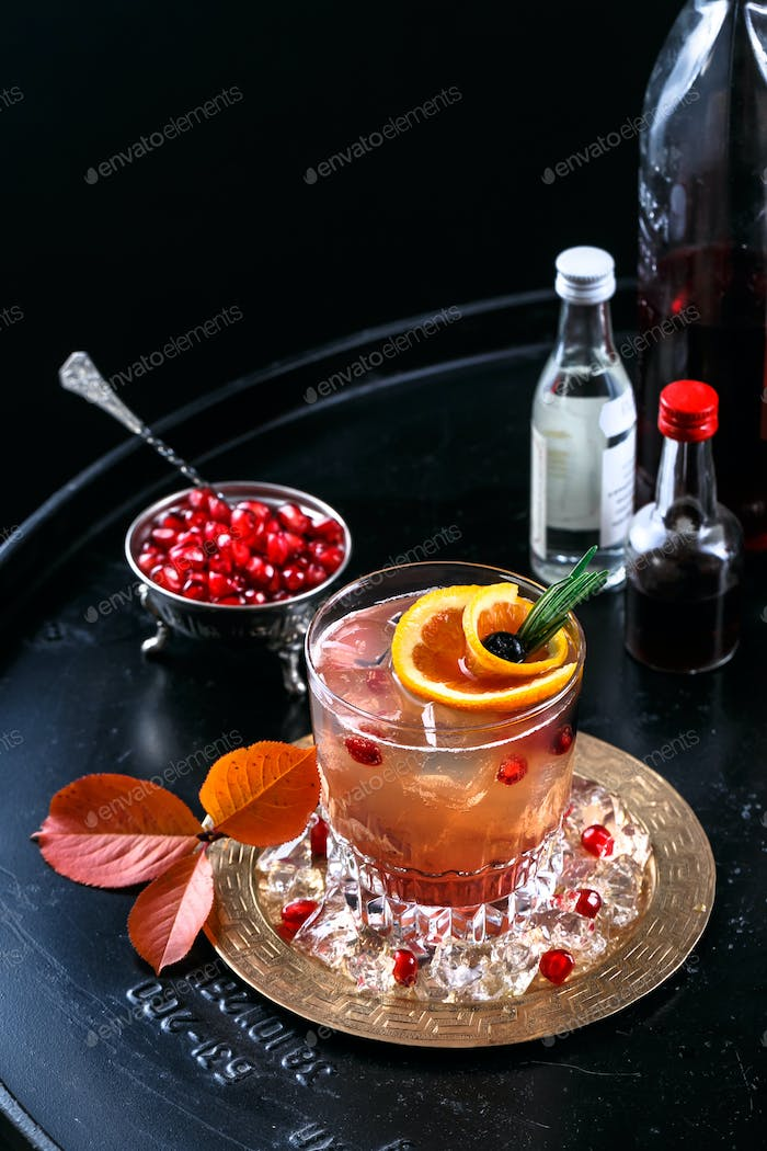 Red alcoholic coctail with vodka and juice on a black background with pomagranate seeds, closeview
