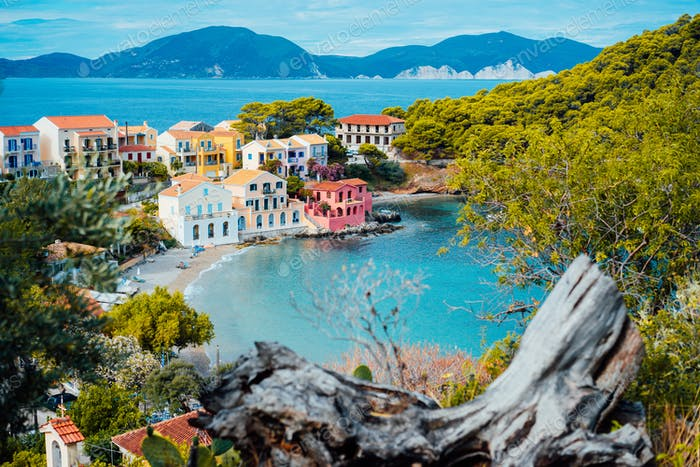 Assos village in Kefalonia, Greece. Calm blue bay water and colored traditional houses. Old snag in